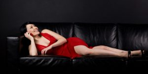 Seductive woman in red reclines on leather sofa