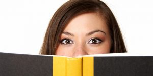 Woman smiles in delight as she peers over the edge of a book
