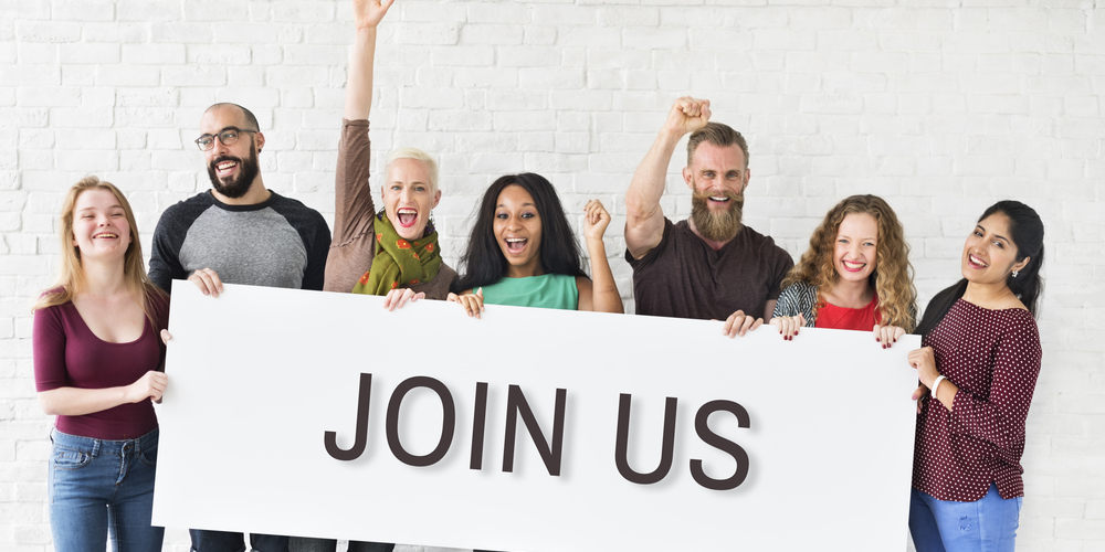 Smiling people hold JOIN US banner