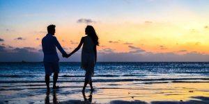 Couple walking on the beach at sunrise
