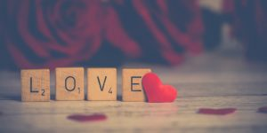 The word LOVE spelled out in Scrabble tiles