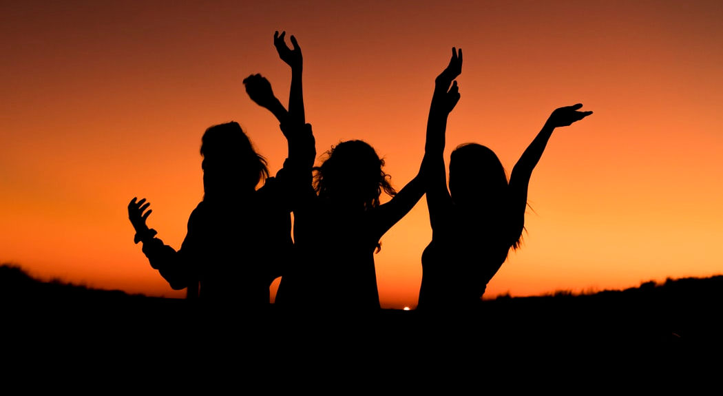 Three women dance silhouetted against the sunset